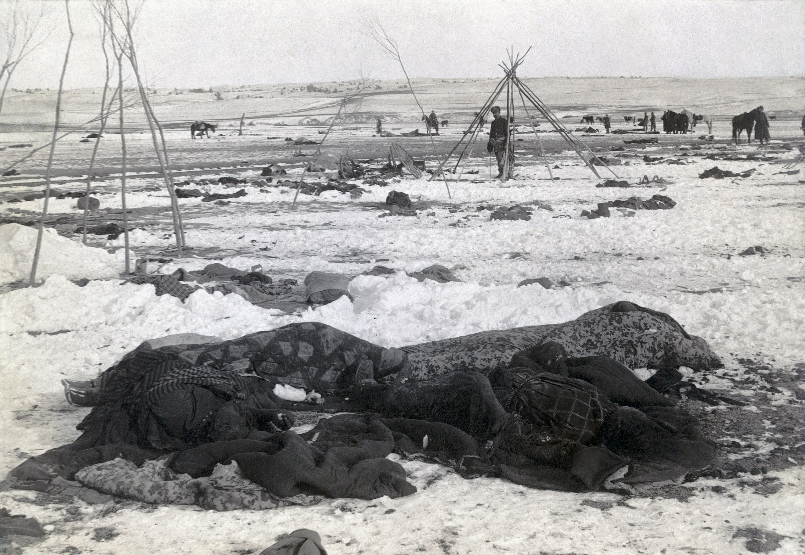 """Public Domain Image: Bibliographic caption: """"Big Foot's camp three weeks after Wounded Knee Massacre; with bodies of four Lakota Sioux wrapped in blankets in the foreground; U.S. soldiers amid scattered debris of camp"""""""